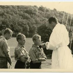 Pastoor Verstyn deelt de communie uit op kamp