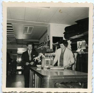 Albert Cleve en vrouw poseren aan toonbank van hun winkel