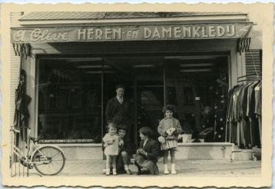 Familie poseert voor stoffen- en kleerwinkel A. Cleve